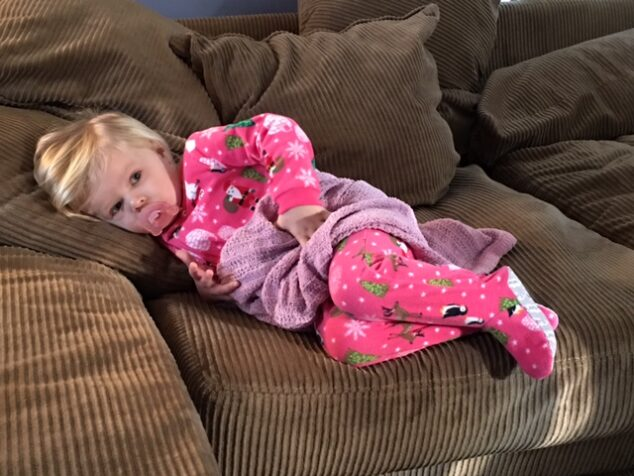 little girl in carters christmas pajamas on brown couch