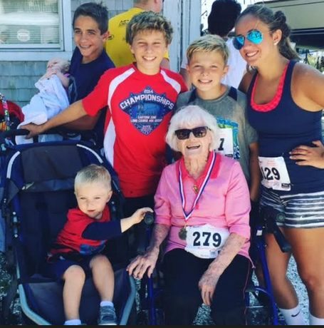 Rita with 6 great-grandkids, 2nd Place Women's Finisher medal around her neck, surrounded with awe and love!