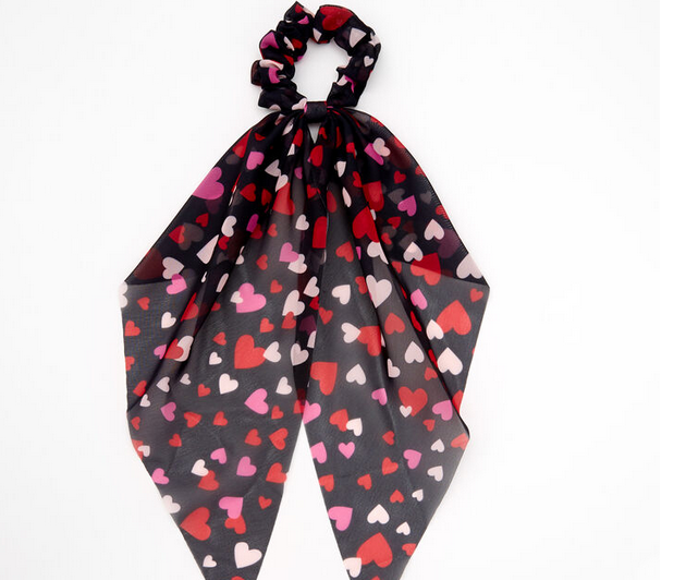 This classic scarf-style hair scrunchie is all dressed up for Valentine's Day! It's printed all over with pink, white, and red hearts.